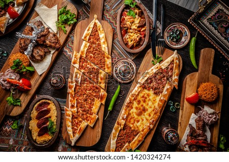 Traditional Turkish cuisine. Pizza, pita, pidesi, sucuk, hummus, kebab, bulgar. Many dishes on the table. Serving dishes in restaurant. Background image. Top view, flat lay ストックフォト ©