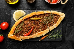 Traditional Turkish cuisine. Turkish pizza on Pita with ground beef on black stone background. top view
