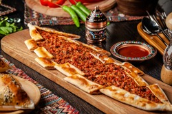 Traditional Turkish cuisine. Turkish pizza Pita with meat. Turk Pidesi or  Sucuk Pide. Beautiful serving dishes in the restaurant. Background image. copy space