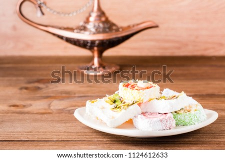 Traditional Turkish Delight on a plate and aladdin lamp on a wooden table. Stockfoto ©