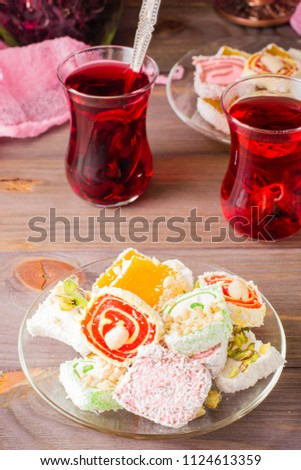 Traditional Turkish Delight on a saucer and hot karkade in cups on a wooden table Stockfoto ©