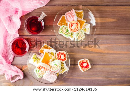 Traditional Turkish Delight on a saucer and hot karkade in cups on a wooden table. Top view Stockfoto ©