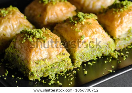 Traditional turkish dessert antep baklava with pistachio on rustic table,  ramadan or holiday desserts concept