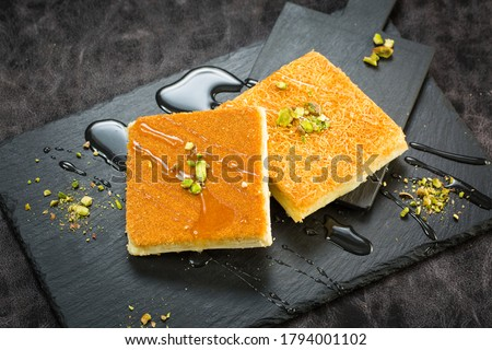 Traditional turkish dessert as known Kunefe or Kunafah or Kunafeh or Kunafa Kadayif. This is middle eastern dessert made pistachio and cream on Black background.