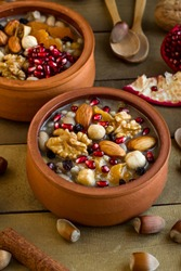 Traditional Turkish Dessert Asure or Noah's Pudding in ceramic casserole bowls on wooden table with wooden spoons and ingredients.Conceptual image of Ashura Day in Islamic Calendar.