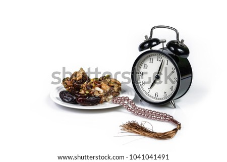 Traditional Turkish dessert Baklava and dried dates fruits on a plate, alarm clock and prayer beads or tasbih isolated on white background. Fasting month Ramadhan concept. #1041041491