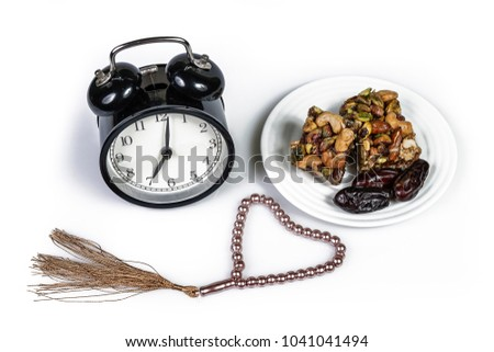 Traditional Turkish dessert Baklava and dried dates fruits on a plate, alarm clock and prayer beads or tasbih isolated on white background. Fasting month Ramadhan concept. #1041041494