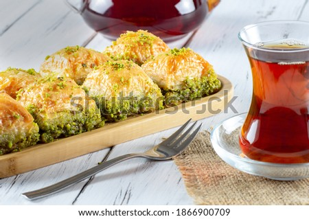 Traditional turkish dessert pistachio antep baklava with turkish black tea on rustic table,  ramadan or holiday desserts concept