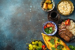 Traditional Turkish food, assorted dishes and mezze appetizers on rustic background from above. Pide, Lahmacun, meat kebab, Turkish meatballs, sweet baklava and Künefe. Middle East cuisine, copy space