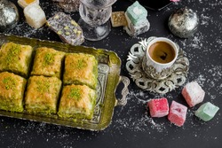 Traditional Turkish Pastry Pistachio Baklava,on vintage tray with coffee and delights.Above view.Conceptual image of celebrations.