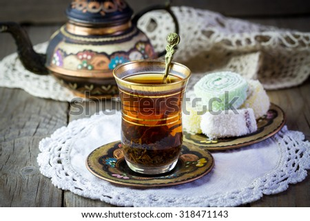Traditional Turkish tea set: glass cup of tea, painted copper teapot, Turkish delight on a plate and vintage napkin on old wooden table
