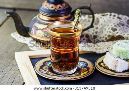Traditional Turkish tea set: glass cup of tea, painted copper teapot, Turkish delight on a plate on wooden background