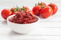 Traditional turkish tomato paste in bowl or spoon with fresh tomatoes on wooden table, homemade healthy food