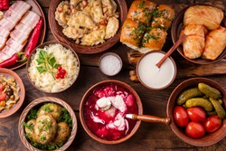 Traditional Ukrainian dishes in clay pots - borsch with sour cream, baked potatoes, garlic pampushki, sauerkraut, lard, canned tomatoes and cucumbers, mushrooms.