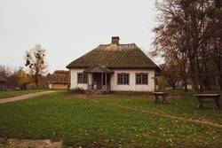 Traditional Ukrainian dwelling of past centuries. Rural house standing in village surrounded by autumn forest.