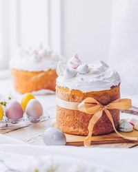 Traditional ukrainian easter cake with white swiss meringue. New cruffin cake trend 2021. Spring cherry blossom and colorful painted eggs. Person decorates cake with hand. Free copy space.