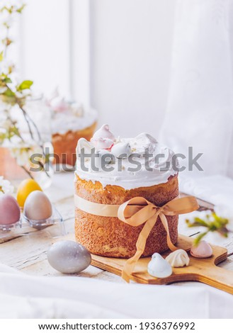 Traditional ukrainian easter cake with white swiss meringue. New cruffin cake trend 2021. Spring cherry blossom and colorful painted eggs. Person decorates cake with hand. Free copy space. ストックフォト ©