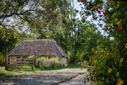 Traditional Ukrainian house with hay roof. Old Ukrainian straw thatched country cottage.