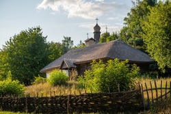 Traditional Ukrainian house with hay roof. Old Ukrainian straw thatched country cottage surrounded with wattle fence.
