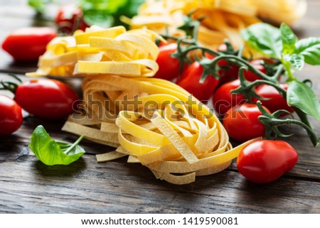 Traditional uncooked italian pasta fettuccine with tomato and basil on the wooden table