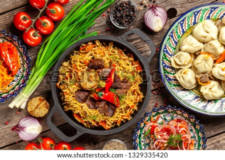 Traditional Uzbek oriental cuisine. Uzbek family table from different dishes in national dishes for the New Year holiday. The background image is a top view, copy space, flat lay