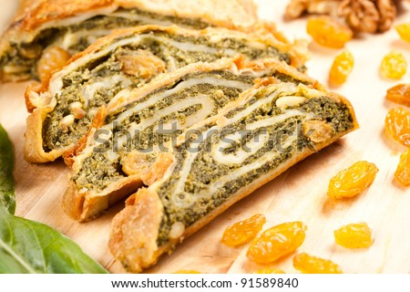 Traditional vegetables strudel pie, homemade and sliced over a wooden board and decorated with raisins and nuts
