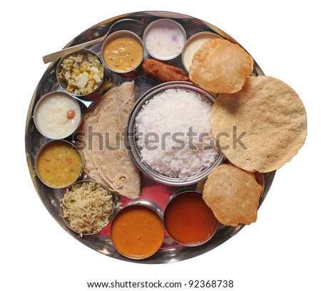 Traditional vegetarian indian thali lunch-  food and meals with rice, phulka(chapatti), puri(poori), curries, sambar, rasam, pulao, papad and sweets isolated on white. Complete nutritional indian food