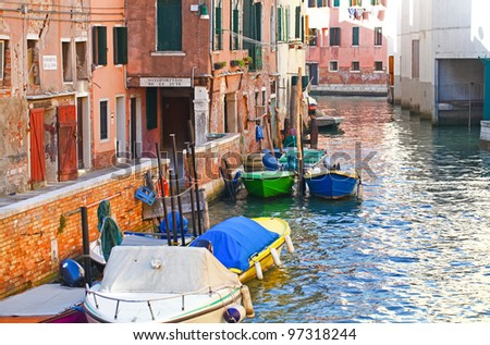 Traditional venetian canal with boats, Italy