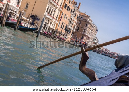 Traditional Venetian vintage boat gondola with an oar in retro forcola on Italy historical buildings and canal blue sky background summer sunny day #1125394664