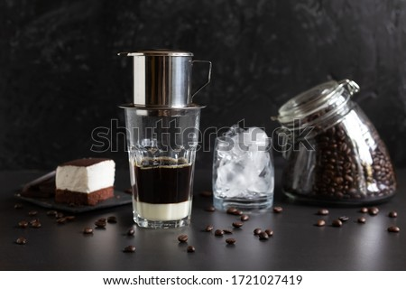 Traditional vietnamese coffee maker  on the top of glass, glass jar with coffee beans, glass with ice and souffle dessert. Iced coffee for summer. Coffee dripping into the glass with condensed milk