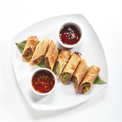 Traditional Vietnamese Deep Fried Spring Rolls, Eggroll or Lumpia with Duck Top View. Crispy Sliced Springroll with Meat, Vegetables and Hot Sauces on a Banana Leaf Isolated on White Background