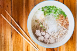 Traditional Vietnamese noodles served in a bowl on a wooden table.