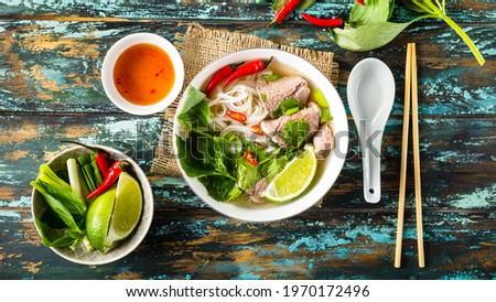 Traditional Vietnamese soup Pho bo with herbs, meat, rice noodles, broth. Pho bo in bowl with chopsticks, spoon. Space for text. Top view. Asian soup Pho bo on wooden table background. Vietnamese soup Stok fotoğraf ©