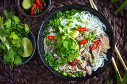 Traditional Vietnamese  soup Pho with beef and rice noodles, top view