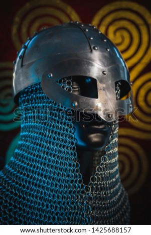 Traditional Vikings, viking helmet with chain mail on a red shield with golden shapes of sun, weapons for war #1425688157