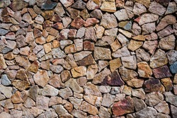 Traditional walls made of piles of broken stones. Antique stonewall.