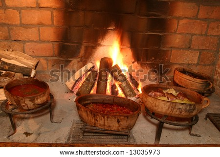 Traditional way of cooking by open fire in clay pot on tripod