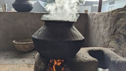 Traditional way of making food on open fire in old kitchen in a village hotel, Rajastha India. Pots and pans on the stove over a natural fire for cooking. Rural kitchen using bio wood fuel for cooking