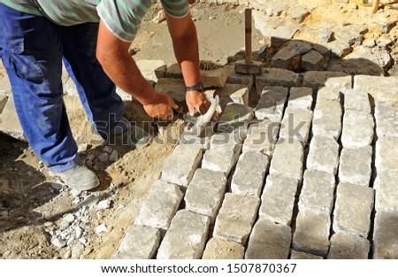 Traditional way of paving a city street with granite cobbles