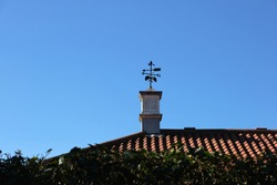 Traditional weather vane or weathercock on the roof. Shrub in the foreground.
