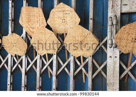 traditional weaved fan, handmade work from bamboo. Thai handcraft against rusty shutter door