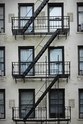 Traditional white apartment facade with black metal fire escapes