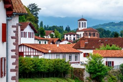 Traditional white houses and church in a basque village in the Pyrenees mountains on spanish border on the Way of Saint James, Saint-Jean-Pied-de-Port, France