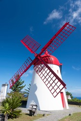 Traditional white wind mill with red roof and wings in village Bretanha, Sao Miguel Island, Azores, Portugal