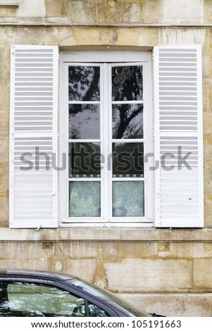 Traditional white window with shutters, seen in Paris, France