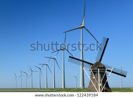 Traditional windmill 'De Goliath' and modern wind turbines in the Eemshaven, the Netherlands.