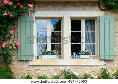 Traditional window with wooden shutters and roses
