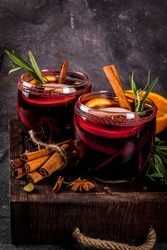 Traditional winter and autumn drinks. Christmas and Thanksgiving Cocktails. Mulled wine with orange, apple, rosemary, cinnamon and spices on a dark stone background, copy space top view