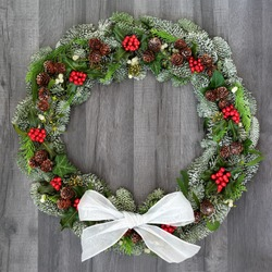 Traditional winter and Christmas natural wreath with bow, holly, snow covered spruce pine fir, mistletoe, pine cones, cedar and ivy leaves on rustic grey wood  background.