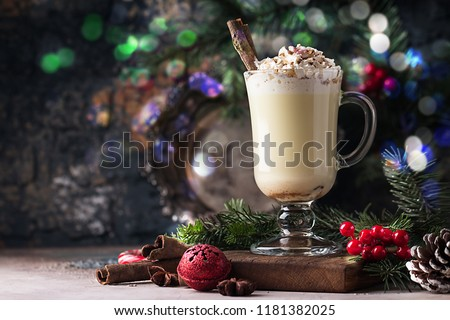 Traditional winter eggnog in glass mug with milk, rum and cinnamon, covered with whipped cream, christmas decorations